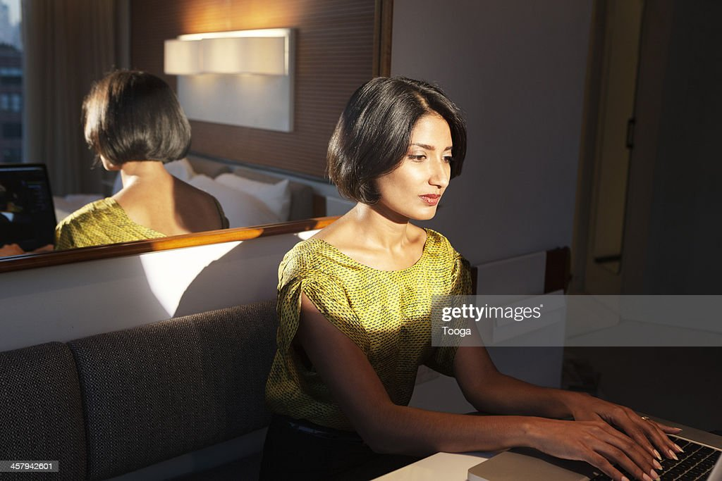 Businesswoman on computer at night : Stock Photo