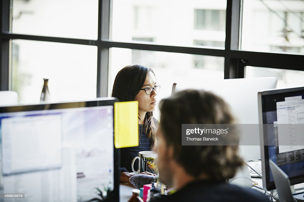 Businesswoman on computer at office workstation : Stock Photo