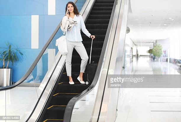 Businesswoman on escalators at airport