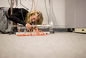 Businesswoman on floor by jumble of wires