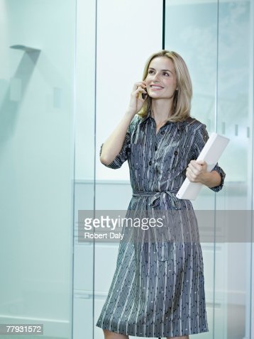 Businesswoman on her mobile phone in office hallway : Stock Photo