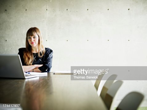 Businesswoman on laptop in conference room