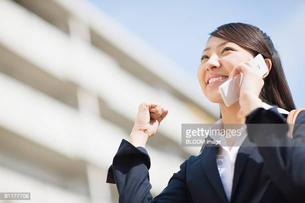 Businesswoman on mobile phone, clenching fist, smiling