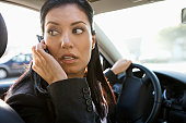 Businesswoman on mobile phone while driving car