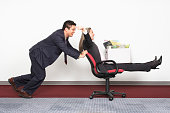 Businesswoman on Office Chair Being Pushed