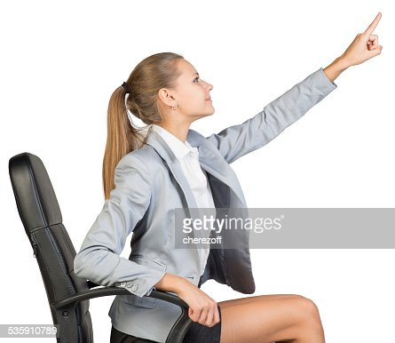 Businesswoman on office chair, pointing finger up and ahead : Stock Photo