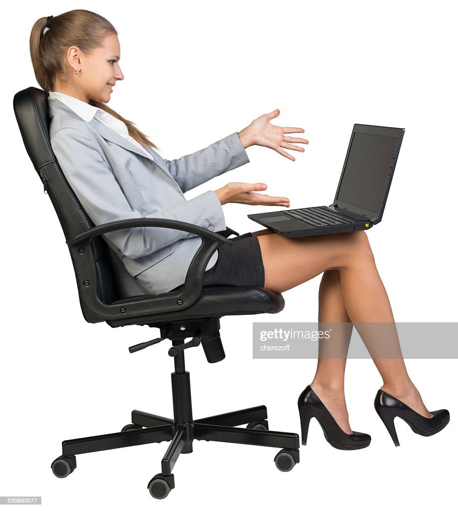 Businesswoman on office chair with laptop, looking and pointing at : Stockfoto