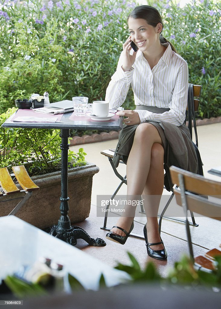 Businesswoman on outdoor patio with her mobile phone : Stock Photo