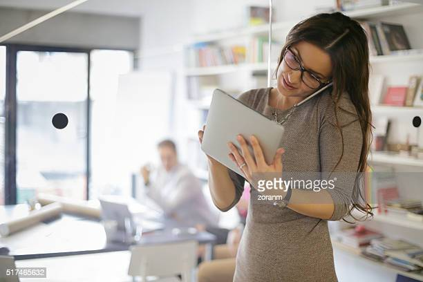 Businesswoman on phone and using digital tablet