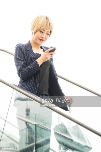businesswoman on phone with baggage on escalator