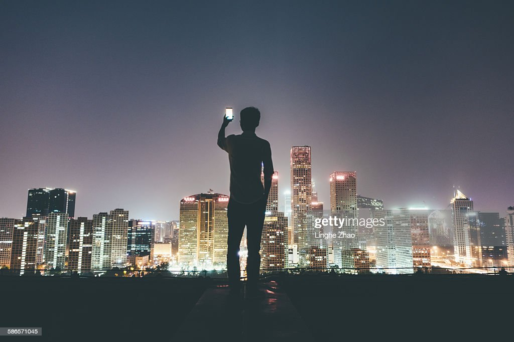 Businesswoman on rooftop holding cell phone : Stock Photo