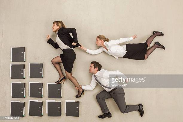 Businesswoman on staircase of files while others chasing