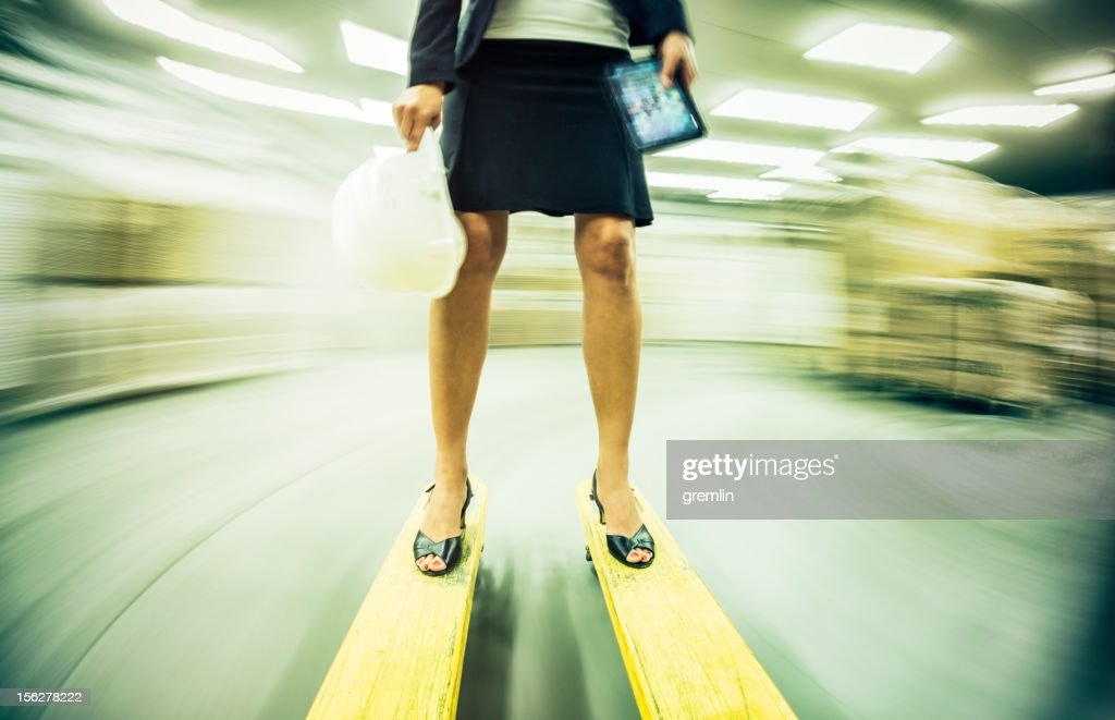 Businesswoman on the speeding forklift in warehouse : Stock Photo