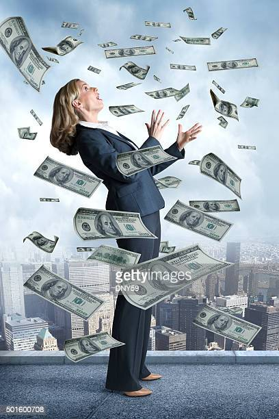 Businesswoman On Top Of Building With Money Raining Down