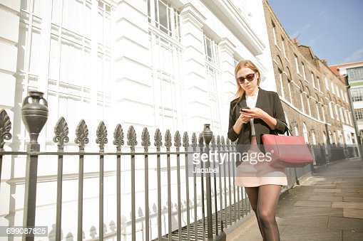 Businesswoman on way to work, using mobile phone, London