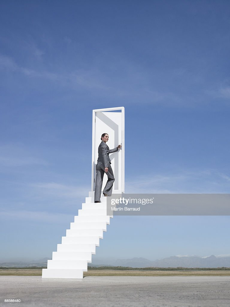 Businesswoman opening door at end of stairway leading to the sky : Stock Photo
