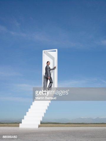 Businesswoman opening door at end of stairway leading to the sky : Bildbanksbilder