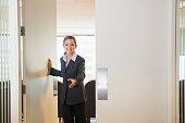 Businesswoman opening door in office