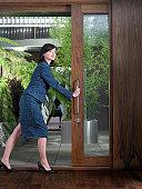 Businesswoman opening door, smiling, looking into distance
