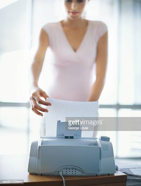 businesswoman operating a fax machine in an office