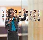 Businesswoman organizing photos of colleagues on touch screen