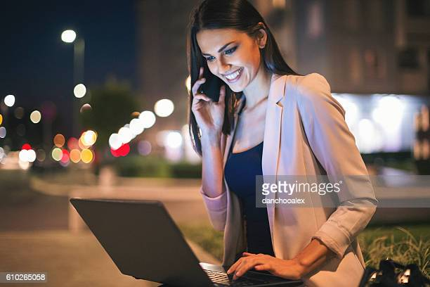 Businesswoman outdoors in the city at night using technology