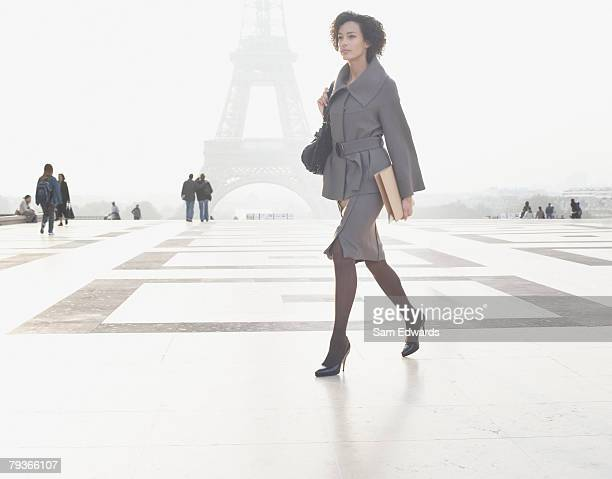 Businesswoman outdoors walking through plaza by the Eiffel Tower