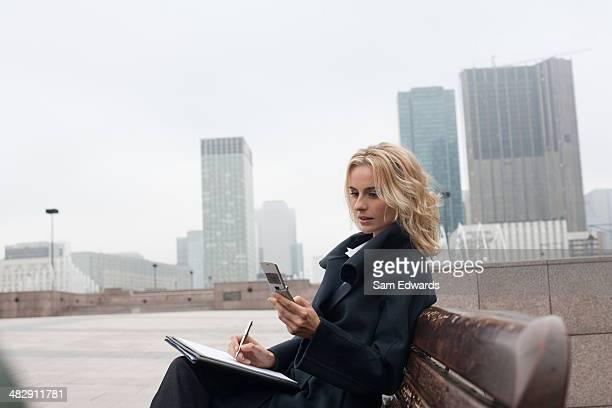 Femme d'affaires à l'extérieur à écrire dans cahier avec celluar téléphone