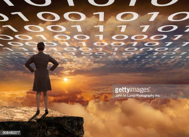 Businesswoman overlooking dramatic clouds with binary code