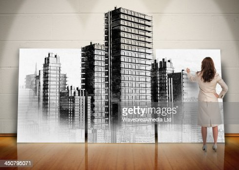 Businesswoman painting black and white city on screen : Stock Photo