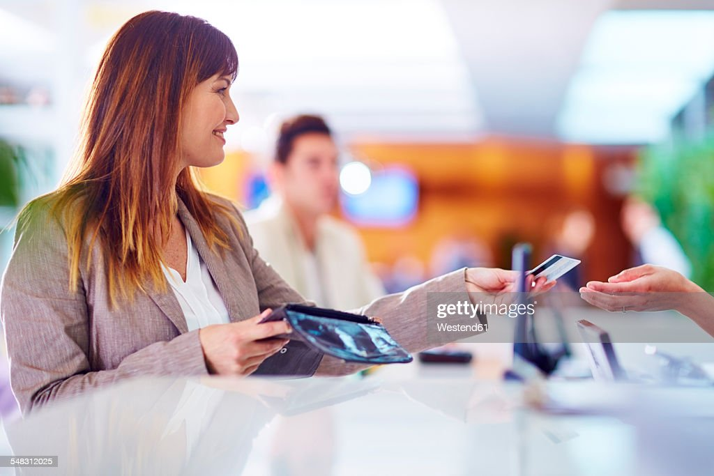 Businesswoman paying with credit card at hotel recption