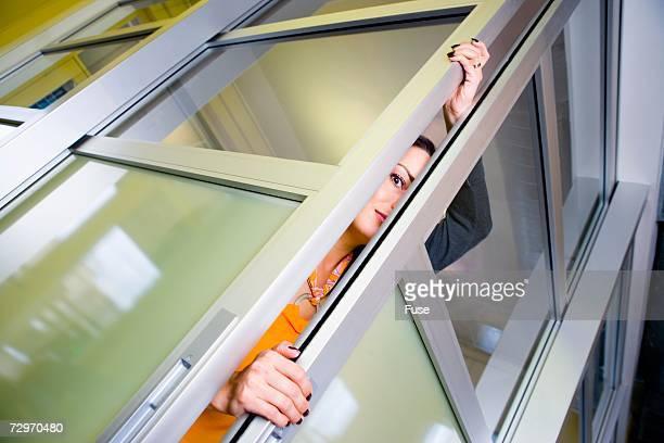 Businesswoman peeking out between sliding doors