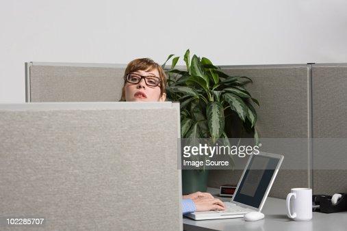 Businesswoman peeking over screen