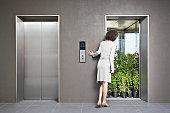 Businesswoman peering at elevator full of plants