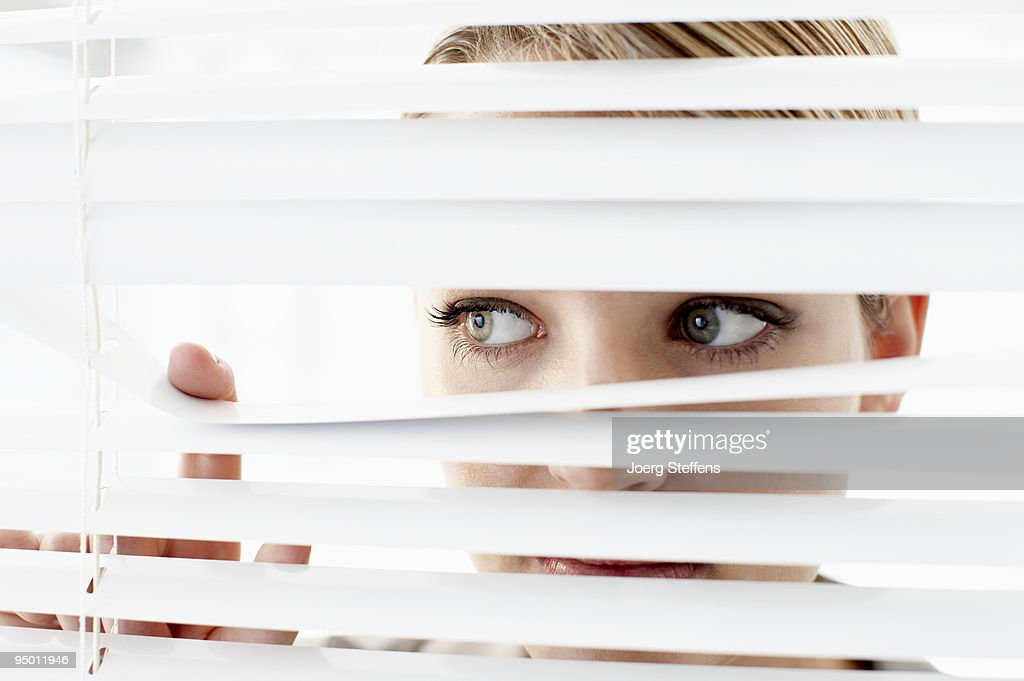 Businesswoman peering through window blinds : Stock Photo