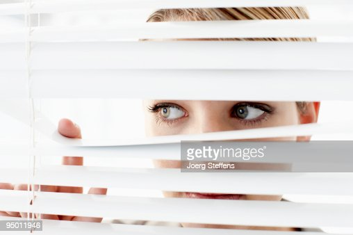 Businesswoman peering through window blinds