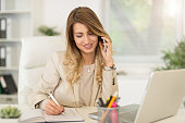 Beautiful young businesswoman sitting in the office, using phone and writing in planner.