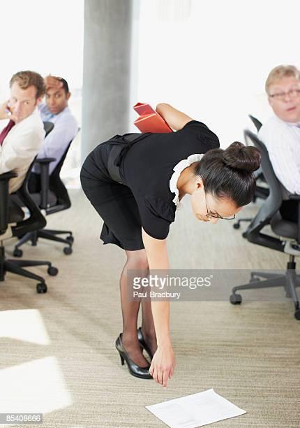 Geschäftsfrau pflücken Papiere vom Etage