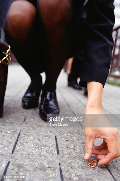 Businesswoman picking up penny on sidewalk, low section