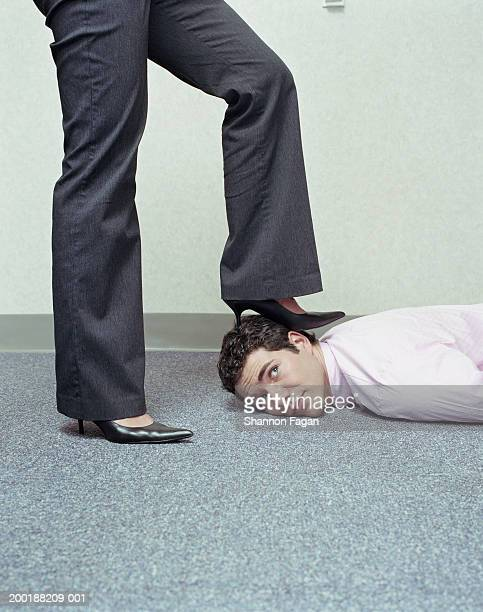 Businesswoman placing foot on man's head, low section, side view