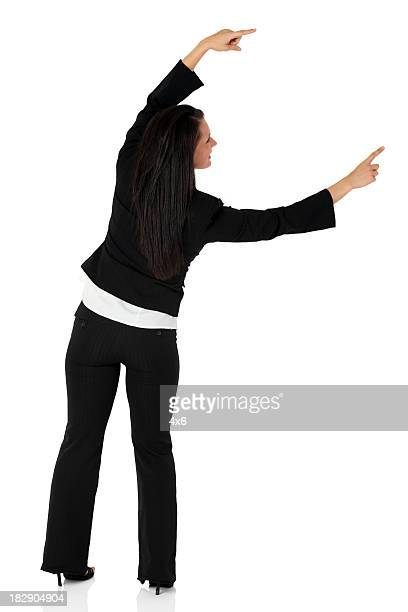 Businesswoman pointing against white background