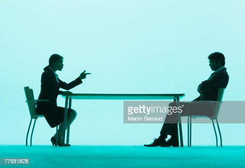 Businesswoman pointing at a businessman at a table : Stock Photo