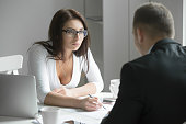 Young boss businesswoman talking to employee, pointing to a mistake in a paper, incorrectly done task by a man or he is missing deadlines, showing authority. Rear view at a man. Business concept photo