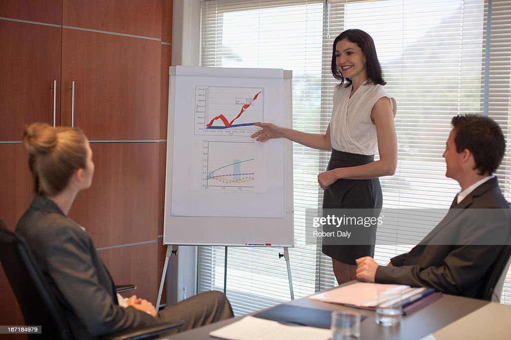 Businesswoman pointing to flipchart in conference room : Stock Photo