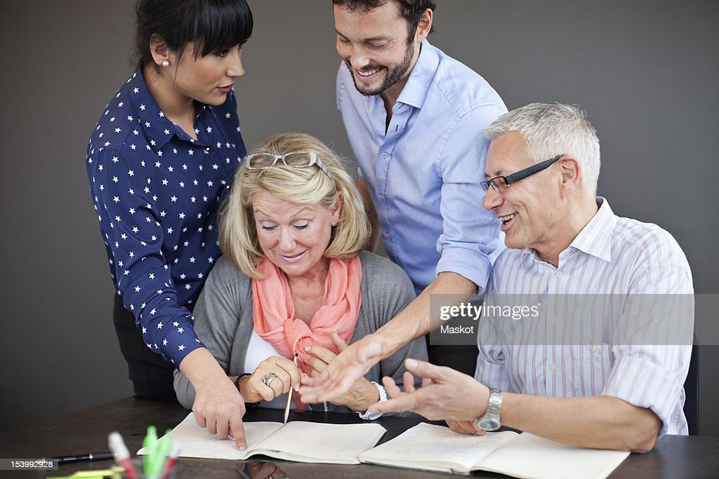 Businesswoman pointing while colleagues smiling in office : Stock Photo