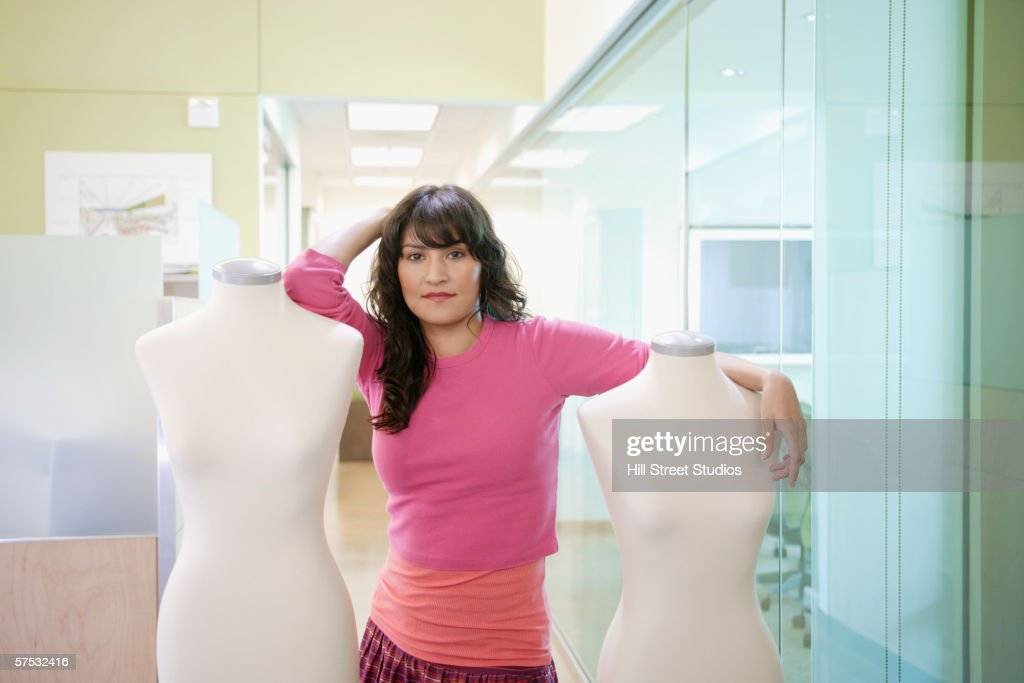 Businesswoman posing for the camera with mannequins : Stock Photo