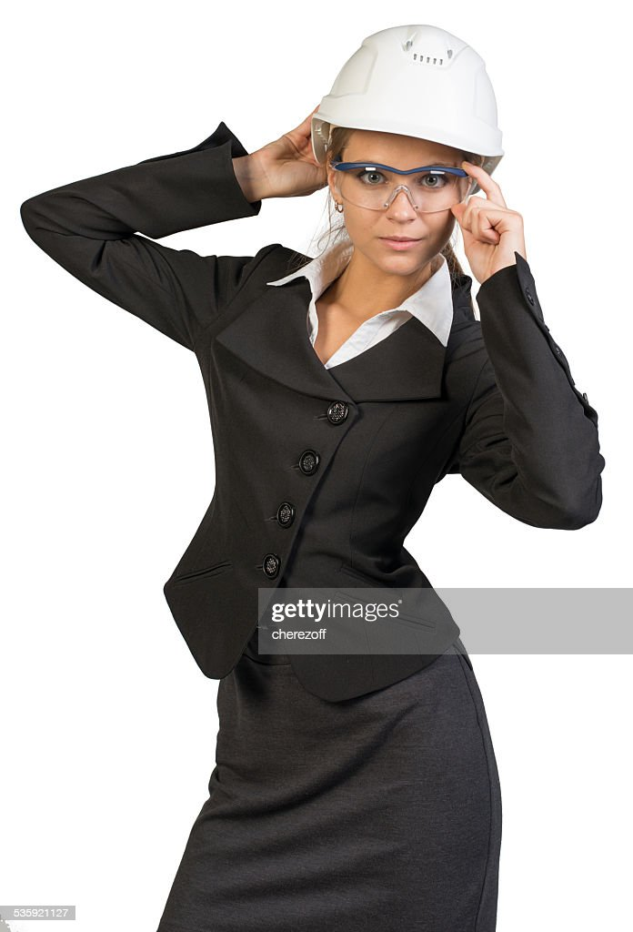 Businesswoman posing in hard hat and protective glasses : Stock Photo