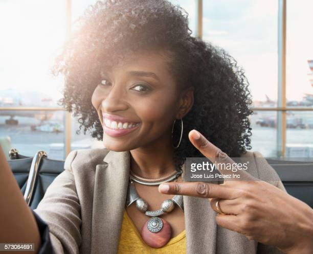 Businesswoman posing with peace sign in airport waiting area