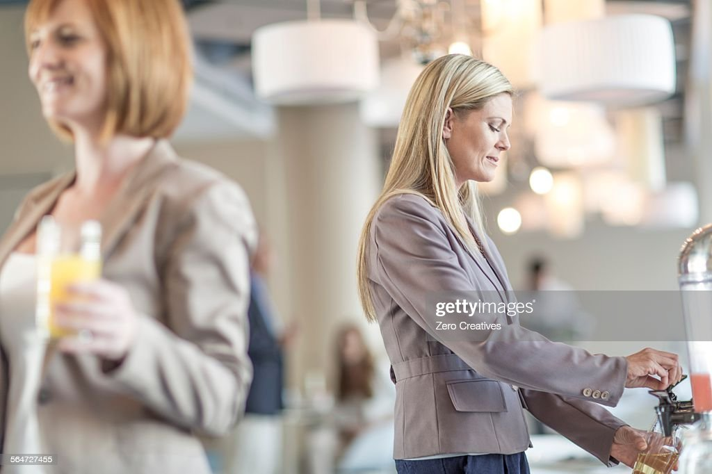 Businesswoman pouring fruit juice in hotel restaurant