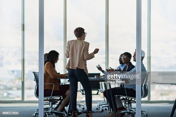 Businesswoman presenting plan in large meeting room